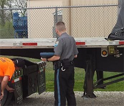 Security guard inspecting flatbed trailer